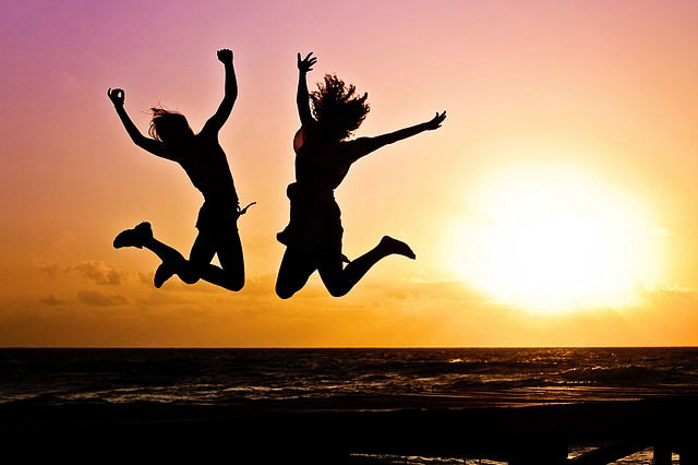 two people jumping in the air`